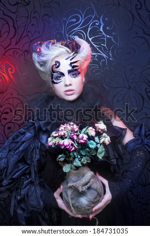 Lady in black. Young woman in creative image and with dry roses. - stock photo