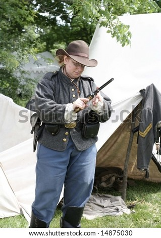 Lady in civil war costume checking her gun - stock photo