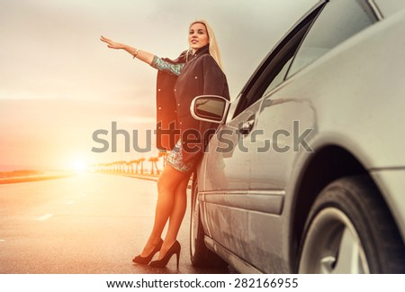 Lady in high heel shoes with broken car on the highway - stock photo