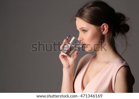 Lady in pink top drinking water. Close up. Gray background