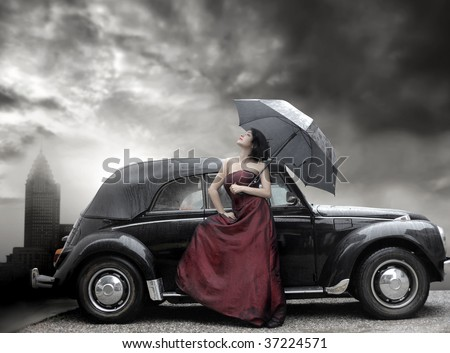 lady in purple dress and holding umbrella next to vintage luxury car - stock photo