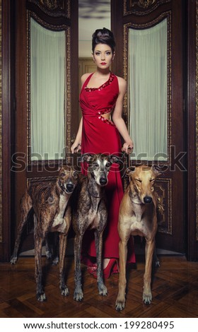 lady in red dress with greyhounds - stock photo
