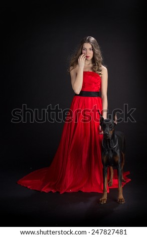 Lady in red with doberman dog in black background - stock photo