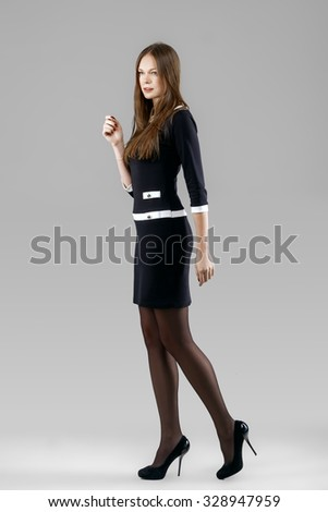 lady in short black dress and high heels posing