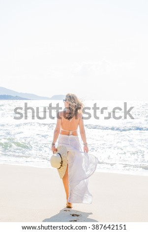 Lady in white relaxing on the tropical beach
