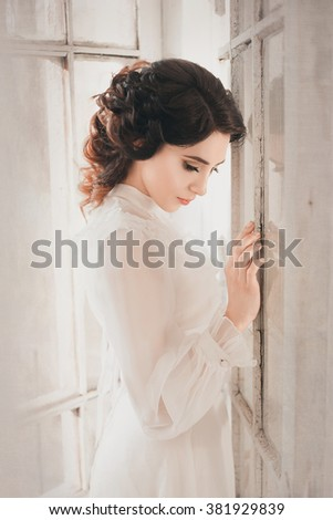 Lady in white vintage dress standing in a large spacious room near the window , fantastic shot, fairytale princess , trendy toning , creative computer colors  - stock photo