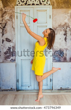 Lady in yellow dress jumps in the room before old white door
