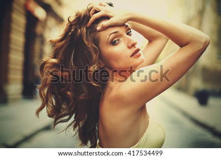 Lady in yellow dress plays with her curly hair