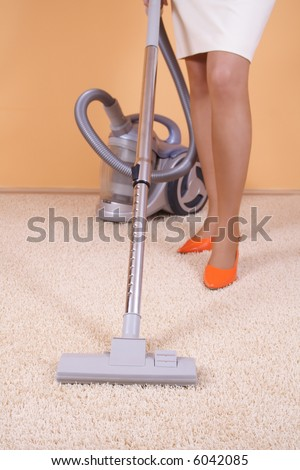 Lady is cleaning carpet - stock photo