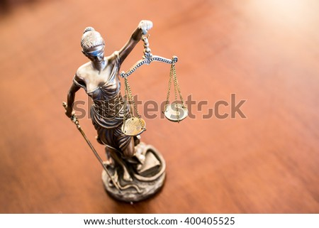 Lady Justice on wooden table - stock photo