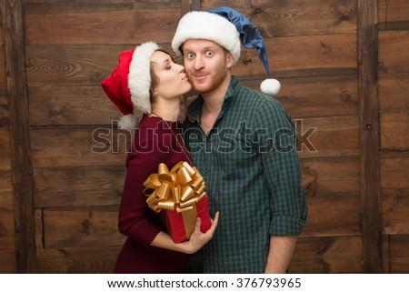 Lady kissing her boy-friend in cheek and holding present for him. Happy man in Santa hat looking at the camera. - stock photo