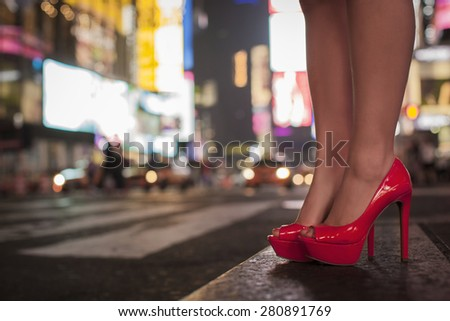 Lady legs with red high heel shoes at Time Square in New York City during night time. - stock photo