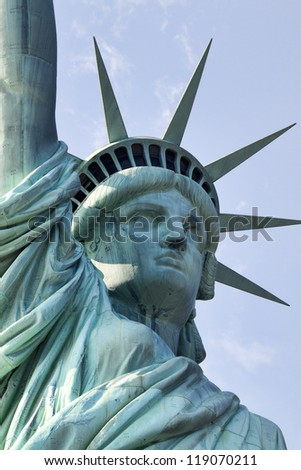 Lady Liberty. Classic close-up image of the upper torso and head of the Statue of Liberty.  The image is shot against a blue sky. - stock photo