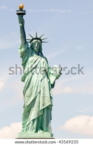 Lady liberty holds her torch against blue New York sky - stock photo