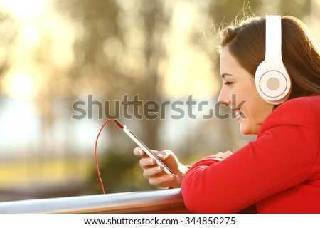 Lady listening music from smart phone with headphones outdoor at sunset in winter - stock photo