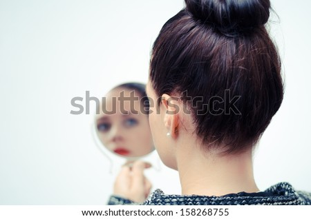 lady looking in a hand mirror with white background - stock photo