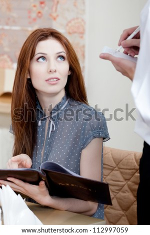 Lady makes an order. The waiter listens to her attentively and white down everything - stock photo