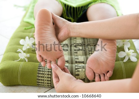 Lady masseur giving female patient a foot reflexology. - stock photo