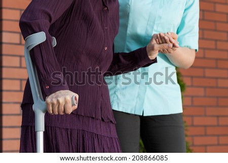 Lady on crutches and nurse in uniform outside the house - stock photo