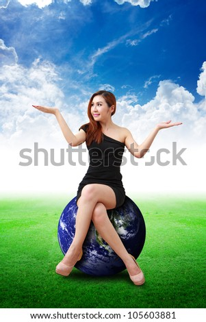 Lady on globe on the grass field : Elements of this image furnished by NASA