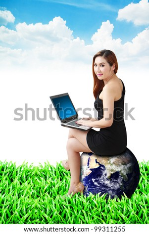 Lady on globe use notebook computer on the grass field : Elements of this image furnished by NASA