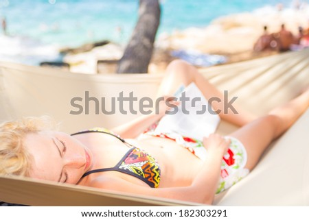 Lady on holidays napping on hammock in pine tree shade on the mediterranean coast. - stock photo