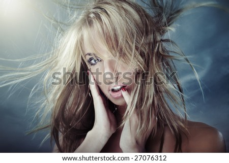 Lady outdoors with long hairs blown by the cooling wind