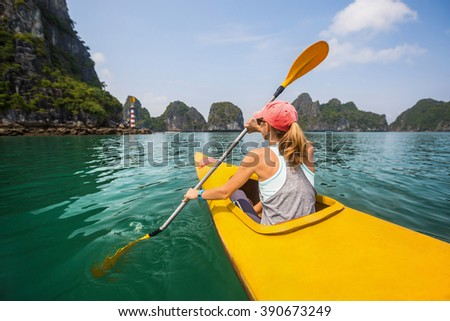 Lady padding on the kayak in the sea near rocks
