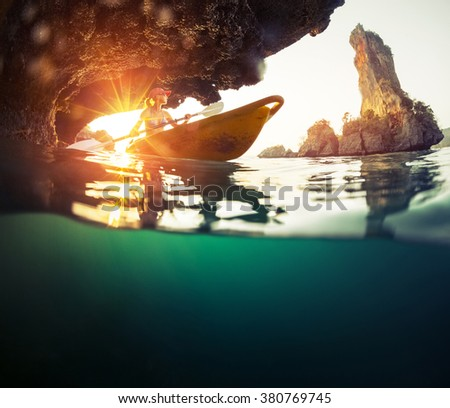Lady paddling kayak in the tropical sea near the rock with underwater view of the sea - stock photo