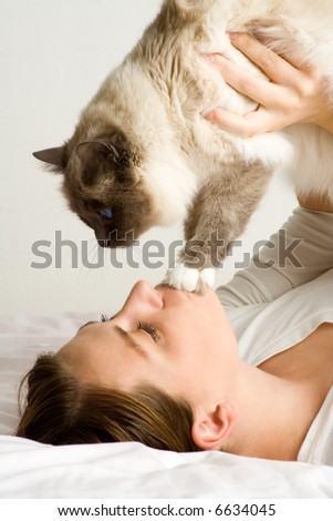Lady playing with cat in bed. Wearing casual white attire. - stock photo