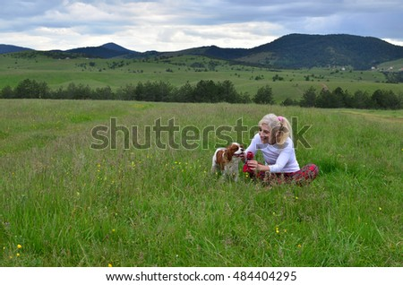 Lady playing with her pet dog (Cavalier King Charles Spaniel) on a green grass with hills and cloudy sky in background
