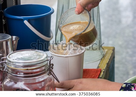 lady pouring fresh coffee ice into paper cap