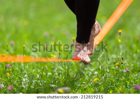 Lady practising slack line in the city park. Slacklining is a practice in balance that typically uses nylon or polyester webbing tensioned between two anchor points. - stock photo