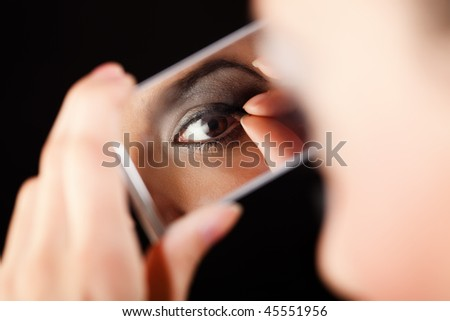 Lady pulling her eyelashes while checking her makeup in the mirror. Selective focus, unrecognizable person.
