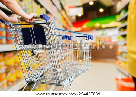 Lady pushing empty shopping cart in the supermarket - stock photo