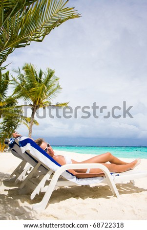 Lady relaxing in the chaise lounge on a exotic resort - stock photo