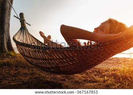 Lady relaxing in the hammock on the beach - stock photo