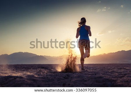 Lady running in the desert at sunset - stock photo