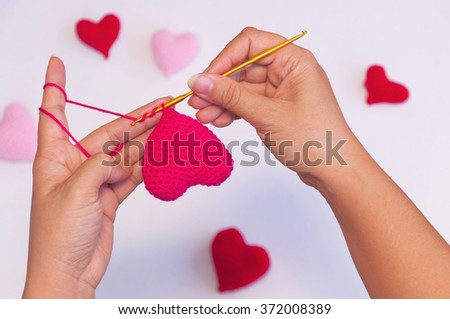 Lady's hands doing crochet work making red heart shape