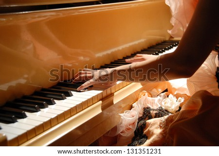 Lady's hands playing the piano in a concert - stock photo