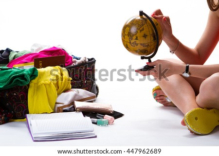 Lady sits beside filled suitcase. Female hand touches small globe. Choose best destination for trip. Many options and opportunities. - stock photo