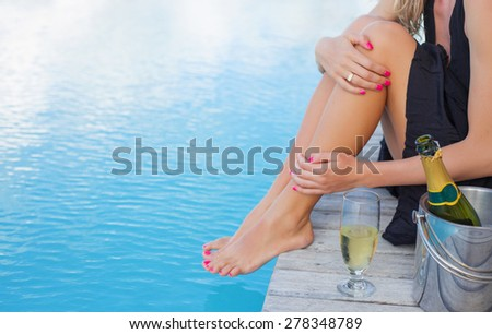 Lady sitting by the pool, focus on champagne glass - stock photo