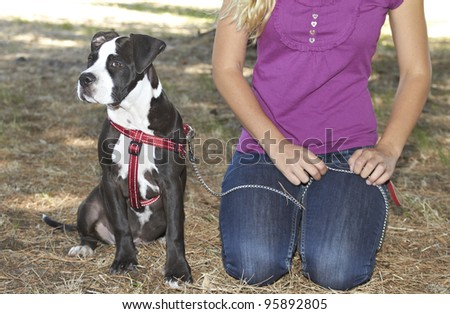 Lady sitting on ground with her Pit Bull puppy