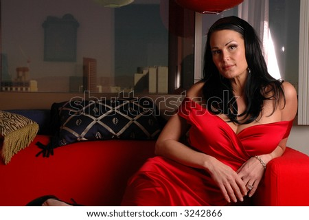 lady sitting on her couch in a red dress