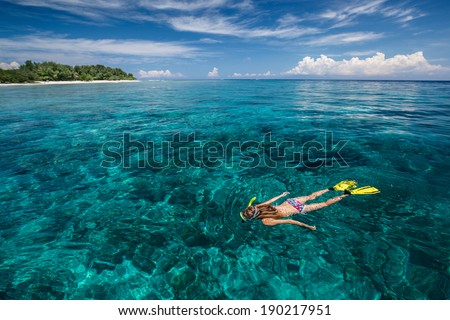 Lady snorkeling in turquoise water near Gili Trawangan island, Indonesia