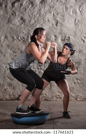 Lady squatting on bosu with boot camp training instructor watching - stock photo