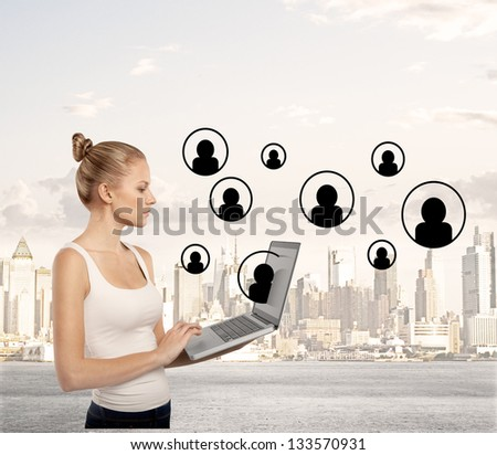 lady standing with laptop on city background - stock photo