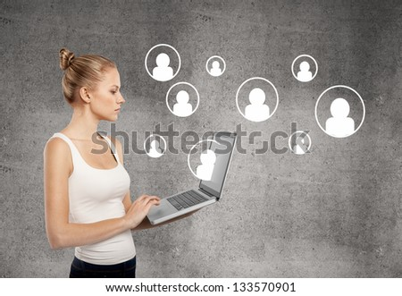 lady standing with laptop on concrete wall background - stock photo