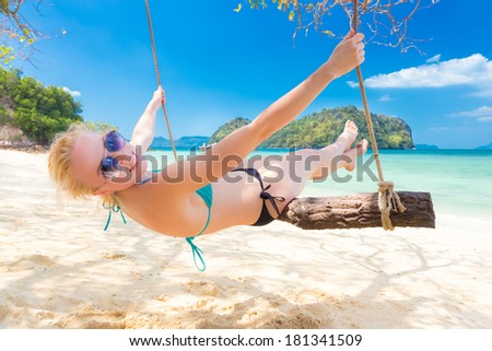 Lady swinging in shade on picture perfect tropical beach with view of island and turquoise coral reef on a sunny summer day. - stock photo