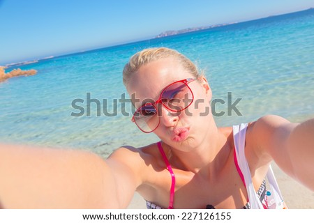 Lady taking a selfie on the beach, sending a kiss from summer vacations. - stock photo